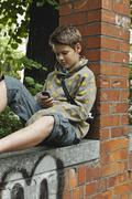 Germany, Berlin, Boy sitting against brick wall with cell phone Stock Photos