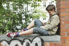Saksa, Berlin, Poika istuu vasten tiiliseinää matkapuhelin Kuvituskuvat