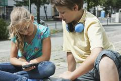 Germany, Berlin, Boy and girl sitting with cell phone and headphone Stock Photos