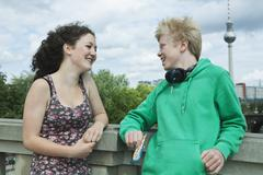 Teenage couple with headphone on bridge - stock photo