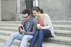 Couple using cell phone on stairway - stock photo