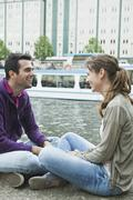 Couple sitting face to face on riverbank Stock Photos