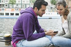 Couple with cell phone on riverbank - stock photo