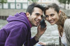 Couple with cell phone on riverbank Stock Photos