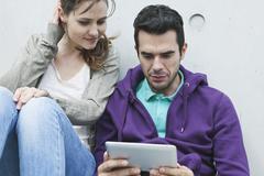 Couple using laptop on stairway - stock photo