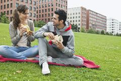 Couple eating food in park - stock photo