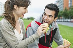 Stock Photo of Couple eating food in park