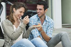 Stock Photo of Couple eating snacks on sidewalk
