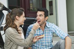 Couple eating snacks on sidewalk Stock Photos