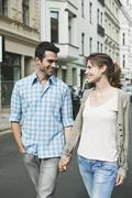 Stock Photo of Couple walking hand in hand through city street