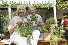 Germany, Bavaria, Man and woman with potted plants - stock photo