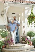 Germany, Bavaria, Mature man and senior woman in front of door, smiling - stock photo