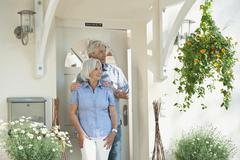 Germany, Bavaria, Man and woman standing at house entrance door Stock Photos