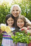 Germany, Bavaria, Granddaughters and grandmother in garden, smiling, portrait Stock Photos