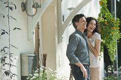 Germany, Couple at entrance of house, smiling Stock Photos