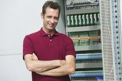 Technician standing with arms crossed by circuit board, smiling, portrait Stock Photos
