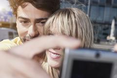 Young couple using cell phone for capturing photo, smiling, close up Stock Photos