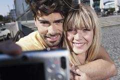 Young couple using cell phone for capturing photo, smiling Stock Photos