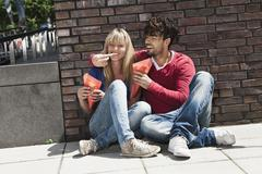 Stock Photo of Young couple eating french fries, smiling