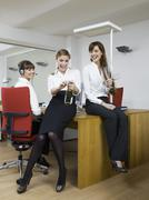 Germany, Cologne, Young women enjoying sparkling wine in office Stock Photos