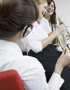 Stock Photo of Germany, Cologne, Young women enjoying sparkling wine in office