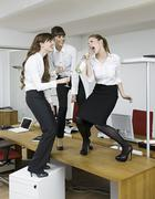 Germany, Cologne, Young women having fun with sparkling wine in office - stock photo