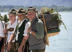 Austria, Salzkammergut, Bad Goisem, Men in traditional costume and birdcage Stock Photos