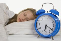 Girl sleeping on bed with alarm clock Stock Photos