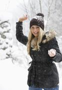 Stock Photo of Austria, Teenage girl with snowball, smiling, portrait