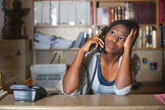 USA, Texas, Young woman having conversation in office Stock Photos