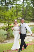 USA, Texas, Bride and groom walking on grass, smiling Stock Photos