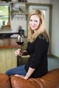 Stock Photo of USA, Texas, Blond woman sitting on sofa, holding glass of red wine
