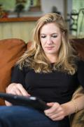 Stock Photo of USA, Texas, Mid adult woman using digital tablet