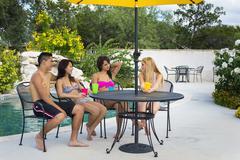USA, Texas, Group of people sitting near swimming pool Stock Photos