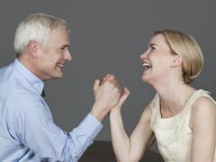 Mature couple arm wrestling, smiling Stock Photos