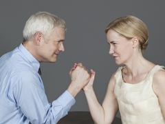 Mature couple arm wrestling Stock Photos