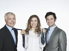 Woman pulling men's tie, smiling Stock Photos