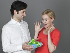 Man giving gift to woman, smiling - stock photo