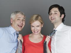 Stock Photo of Woman pulling men's tie, smiling