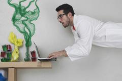 Young man doing experiment and using laptop - stock photo