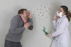 Patient sneezing with doctor Stock Photos