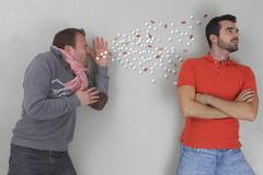 Man sneezing with young man looking away - stock photo