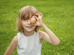 Germany, Brandenburg, Girl holding egg in front of eyes - stock photo