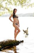 Stock Photo of Germany, Brandenburg, Young woman in bikini at lake, smiling, portrait