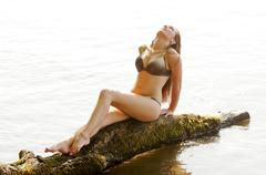 Stock Photo of Germany, Brandenburg, Young woman sitting on wood in lake