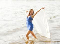 Germany, Brandenburg, Young woman holding transparent cloth on lake - stock photo