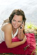 Stock Photo of Germany, Brandenburg, Young woman using mobile on lakeshore, smiling