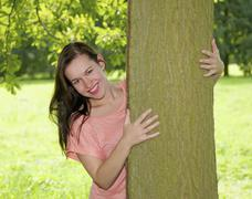 Germany, Berlin, Young woman embracing tree trunk, smiling, portrait - stock photo