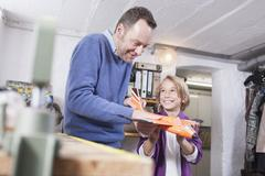 Germany, Leipzig, Father and son repairing toy plane - stock photo