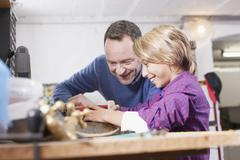 Germany, Leipzig, Father and son repairing skateboard - stock photo
